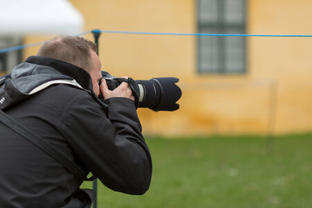 Close-up of male photographer using his camera outdoors. Stock Photo