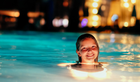 Tanned caucasian girl in a resort swimming pool during night.