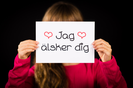 jag: Studio shot of child holding a sign with Swedish words Jag Alsker Dig - I Love You Stock Photo