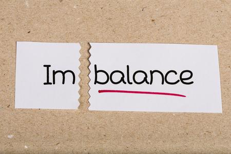 imbalance: Twee stukken van wit papier met het woord onbalans omgezet in balans