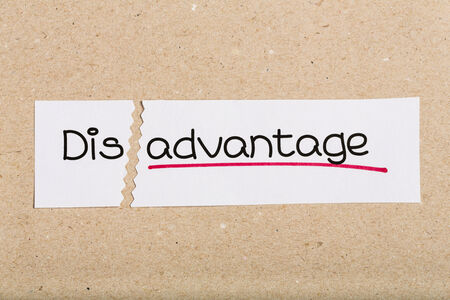 disadvantage: Two pieces of white paper with the word disadvantage turned into advantage