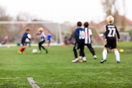 녹색 잔디에 아이들이 축구 훈련 세션 동안 젊은 백인 소년.
