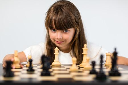 ajedrez: Muchacha cauc�sica joven con el pelo largo que juega una partida de ajedrez. Foto de archivo