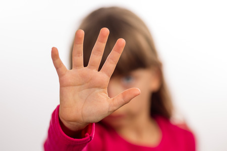 Young girl making stop gesture with her hand. Focus is on the hand. The face of the girl is blurred.