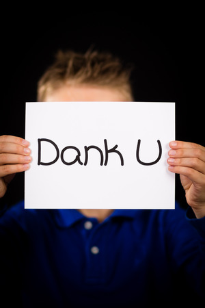 dank: Studio shot of child holding a sign with Dutch words Dank U - Thank You Stock Photo
