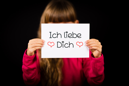 Liebe: Studio shot of child holding a sign with German words Ich liebe Dich - I Love You