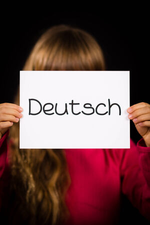 deutsch: Studio shot of child holding a sign with German word Deutsch - German in English