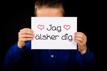 jag: Studio shot of child holding a sign with Swedish words Jag Alsker Dig - I Love You Stock Photo