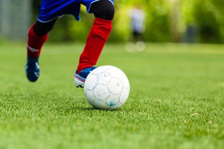 축구 공을 드리블하는 젊은 축구의 그림.