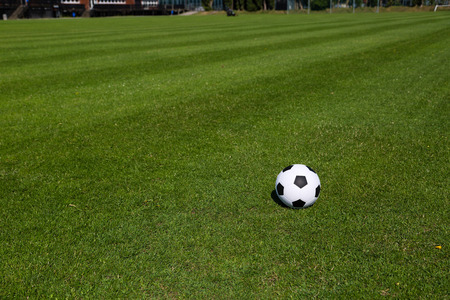 soccer pitch: Black and white soccer ball on green soccer pitch. Stock Photo