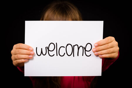 welcome people: Studio shot of child holding a Welcome sign made of white paper with handwriting.