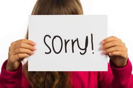 sorry: Studio shot of child holding a Sorry sign made of white paper with handwriting. Stock Photo
