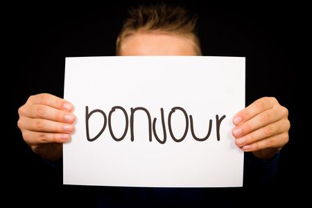 bonjour: Studio shot of child holding a sign with French word Bonjour - Hello