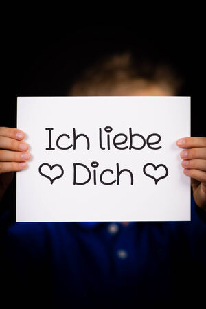 in liebe: Studio shot of child holding a sign with German words Ich liebe Dich - I Love You