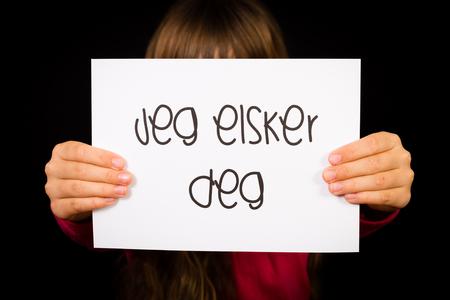deg: Studio shot of child holding a sign with Norwegian words Jeg Elsker Dig - I Love You