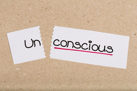 the unconscious: Two pieces of white paper with the word unconscious turned into conscious