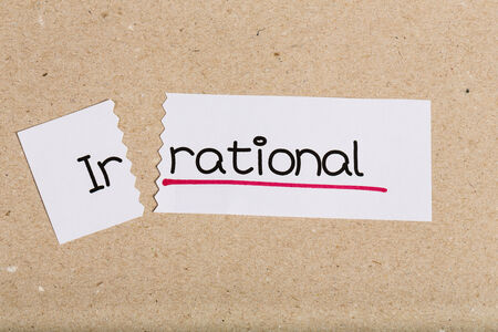 Two pieces of white paper with the word irrational turned into rational Stock Photo