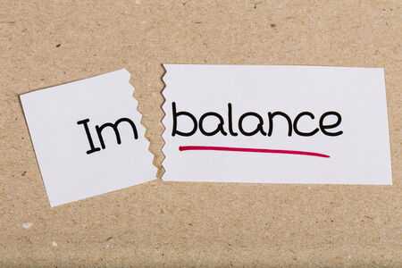 imbalance: Two pieces of white paper with the word imbalance turned into balance