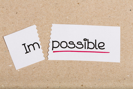 Two pieces of white paper with the word impossible turned into possible Stock Photo