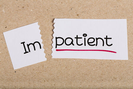 impatient: Two pieces of white paper with the word impatient turned into patient