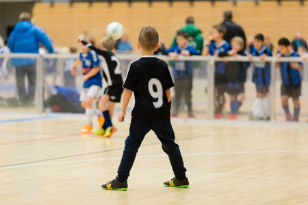 Young northern european boys playing a indoors soccer training match inside an indoor sports arena.