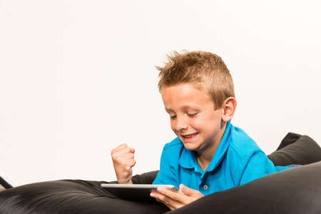 beanbag: Boy lying down on beanbag with his tablet. Studio shot on white background. Stock Photo