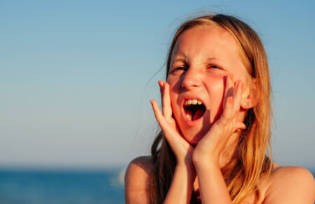 cry for help: Tanned caucasian girl shouting for help on a sunny summer day. Stock Photo
