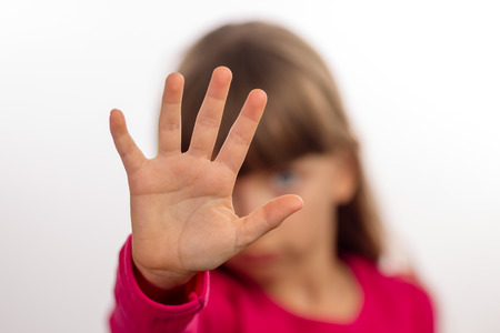stop hand: Young girl making stop gesture with her hand. Focus is on the hand. The face of the girl is blurred.