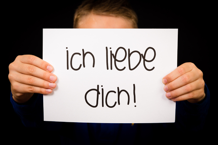 i kids: Studio shot of child holding a sign with German words Ich liebe Dich - I Love You