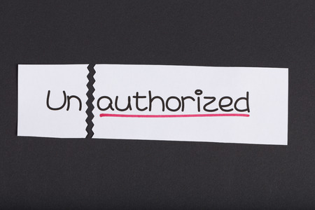 unauthorized: Two pieces of white paper with the word unauthorized turned into authorized