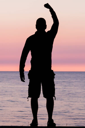 self realization: Silhouette of male person against a colorful horizon. Stock Photo