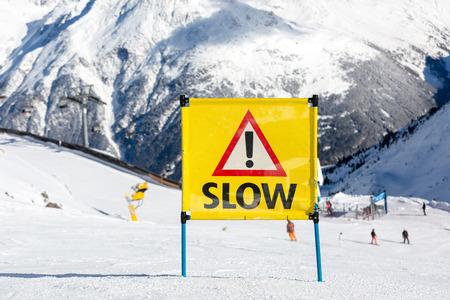 skipiste: Gelb Warnung Schild mit dem Text langsam und Ausrufezeichen auf Skipiste am Skigebiet platziert.