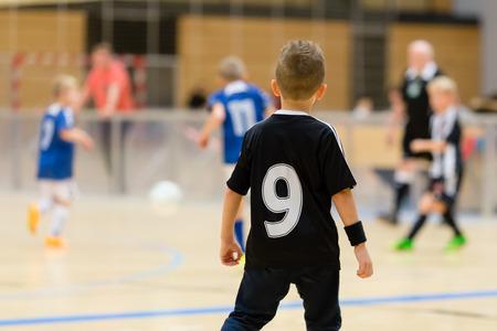 Fiatal észak-európai fiúk játszanak bent foci képzés mérkőzés belsejében egy fedett sportcsarnokban.