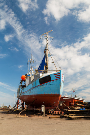 drydock: Medium-sized fishing boat standing in a drydock for repairs.