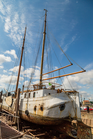 drydock: Large old sailing boat undergoing serious repair work while docked on the quay.