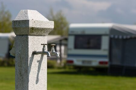 camping site: Outdoors water tap at camping site on a sunny day. Blurry caravan in the background. Stock Photo