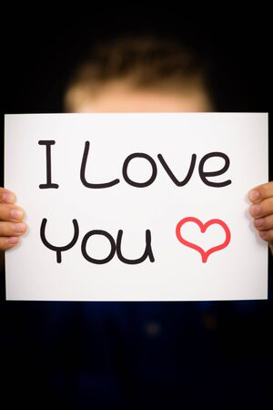 i love you sign: Studio shot of child holding an I Love You sign made of white paper with handwriting.