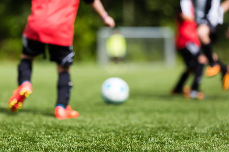 soccer ball on grass: Picture of kids soccer training match with shallow depth of field. Focus on foreground.