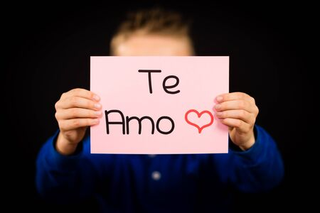 i kids: Studio shot of child holding a sign with Spanish words Te Amo - I Love You