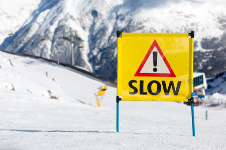 piste: Yellow warning sign with the text slow and exclamation mark placed on ski piste at ski resort. Stock Photo