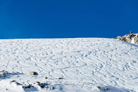 freeride: Ski slope with fresh powder snow and off piste tracks made by skiers and snowboarders. Stock Photo