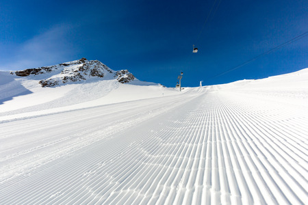 Neve fresca su pista da sci di recente curato a stazione sciistica delle Alpi in una giornata invernale di sole.