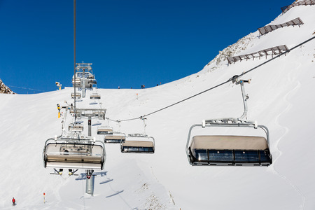 chair on the lift: Ski resort in the Alps with chair lift and ski slope with descending skiers. Stock Photo