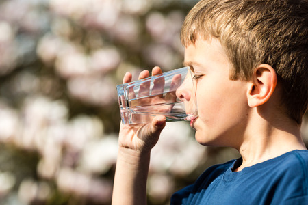 the water: Young boy drinking from glass of fresh water. Ideal for environmental protection or future generations concept. Stock Photo