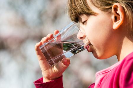 어린 소녀 잔을 들고와 순수한 물을 마시는. 환경 보호 또는 미래 세대 개념에 적합합니다.