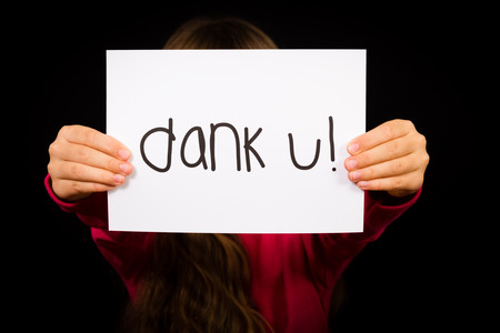 dutch girl: Studio shot of child holding a sign with Dutch words Dank U - Thank You Stock Photo