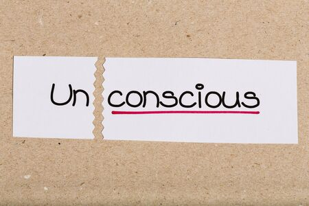 Two pieces of white paper with the word unconscious turned into conscious