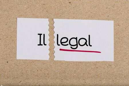 underscore: Two pieces of white paper with the word illegal turned into legal