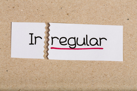 underscore: Two pieces of white paper with the word irregular turned into regular
