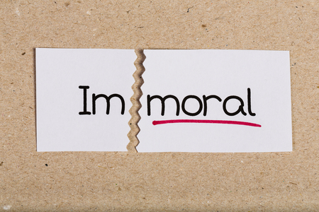 Two pieces of white paper with the word immoral turned into moral Stock Photo